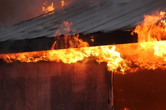 Flames rise over eaves